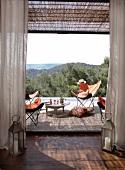 Laternen-Windlichter als Wächter der Terrassentür; Weitblick von der Terrasse mit einladenden Fledermaussesseln und Drinks auf Tabletttisch