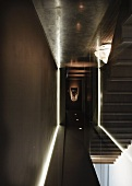 Minimalist hallway with indirect lighting and view of staircase through glass partition