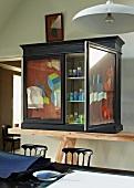Apothekerflaschen mit Färbemitteln in einem alten Apothekerschrank mit Kunstmalerei an den Türen
