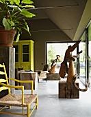 Holzskulpturen im Raucherzimmer mit schlammgrüner Wandfarbe