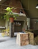 Baumstamm-Möbel und ein alter Kamin mit einem Kerzenleuchter im Raucherzimmer mit schlammgrüner Wandfarbe