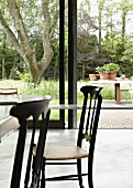 Dining table and Chiavari chairs in front of sliding glass doors leading to garden