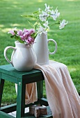 Two jugs of flowers on wooden stool in garden