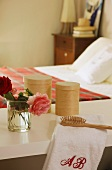 Roses, towel, hairbrush and containers on shelf in bedroom