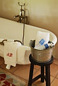 Bathtub with antique brass tap fittings and bucket of toiletries on stool