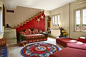 Comfortable, red sofa combination and colourful, ethnic-style rug in simple interior with staircase