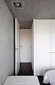 Weisses Interieur und Sichtbeton im minimalistisch kühlen Schlafraum
