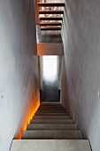 Stairwell in concrete house - monolithic concrete stairs with indirect, coloured lighting and cantilever treads