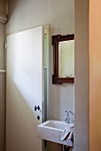 Small stone sink and antique, framed mirror next to white, country-house door