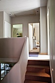 Stairs and landing with organically-shaped balustrade wall; open interior doors in background