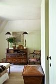 Gemütliches Mansarden-Schlafzimmer mit Antikmöbeln - Armlehnstuhl neben Sekretär unter modernem Gemälde und auffallend hohe Tischlampen
