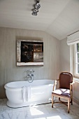 Bathroom with attic ceiling and veined marble floor; modern painting over free-standing bathtub next to antique upholstered chair