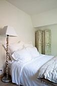 Einfaches Mansardenzimmer mit klassisch weiss bezogenem Bett, abgeblättertem Paravent an der Wand und Stehlampe im antiken Vintagelook