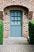 Blau lackierte Eingangstür in Fassade aus Klinkersteinen