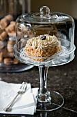 Törtchen mit Sahne und Kaffeebohne verziert unter Glashaube auf Glasschale mit Fuss