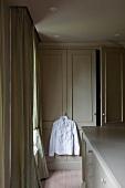 Ankleidezimmer - Weisses Hemd auf Kleiderbügel an Griff einer Schranktür aufgehängt