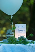Menu card for summer party on river bank; names written on stacked pebbles, balloon and fennel fronds as table decoration