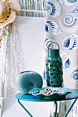 Mint green ceramic lantern on small side table; straw hat and curtain with shell design in background