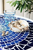 DIY balcony table with mosaic tiles in shades of blue and decorative collection of seashells