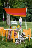 Hand-sewn awning stretched between bamboo canes above set table with orange armchairs; Dalmatian in foreground and woman in blurred background