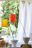 Small paper lanterns attached to wooden canes with clothes pegs in garden setting with white curtain in background