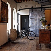Bicycle parked in foyer of renovated villa with arched windows