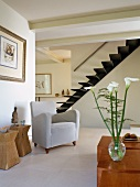 Open-plan living with mixture of furniture styles and view of modern staircase