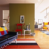 Leather sofa on rug in open-plan interior with kitchen in cubist installation