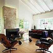 Classic items of furniture in contemporary interior - easy chairs, black leather couch and glass table on castors in front of open fireplace