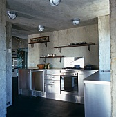 Open-plan kitchen with unfinished ambiance and retro ceiling lamps above stainless steel kitchen counters