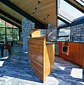 Open-plan interior - kitchen and free-standing, boat-shaped kitchen counter on dynamically patterned stone floor
