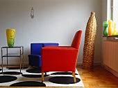 Simple, red armchair on rug in modern design and rattan floor vase in corner of living room