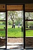 Blick durch offene Glastür eines modernen Wohnhauses auf Frau im frühlingshaften Garten