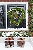 Fassadenausschnitt - Herzförmiger Kranz vor Fenster aufgehängt und Aufbewahrungskörbe mit Pinienzapfen im Schnee
