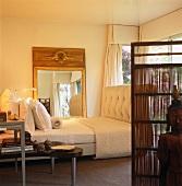 Sleigh bed in front of gilt-framed, full-length mirror on bedroom