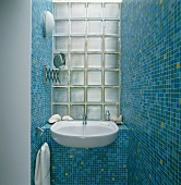 Blue mosaic wall tiles and washbasin against glass brick wall in small bathroom