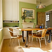 Modern chairs with rattan backs and seats around table on castors in traditional dining room