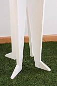 Detail of white-painted, wooden coat rack on green, artificial lawn rug