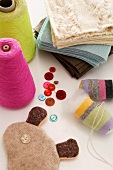 Colourful spools of thread, buttons and knitted fabrics on white surface