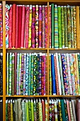 Various patterned fabrics on wooden shelves