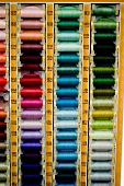 Spools of thread in various colours arranged in rack