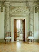 Walls painted with ancient Greek architecture motifs next to open double doors and wooden chairs with light upholstered seats
