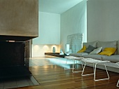 White metal stools in front of sofa and fireplace in modern interior