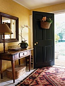 Antique wooden table against yellow-painted wall and patterned rug in front of open front door