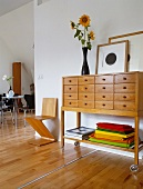 Sideboard with drawers on castors in open-plan foyer with view into living room