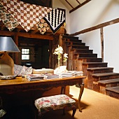 Antique wooden table, open staircase and gallery with ethnic textiles hung over balustrade