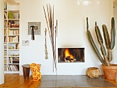 Large potted cactus next to open fire in modern interior