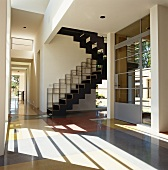 Open-plan foyer with contemporary staircase and front door made of metal and glass