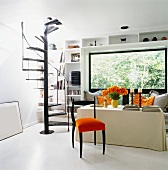 Chair with orange seat cushion in front of table with fitted cover and black-painted, metal spiral staircase in modern interior