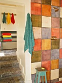 Rustic bathroom with multi-coloured tiles on wall next to doorway with steps and view of stack of coloured towels